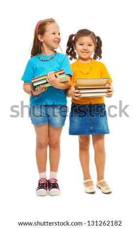Two happy little girls Asian and Caucasian black and light haired with stack books standing isolated on white, full height portrait - stock photo