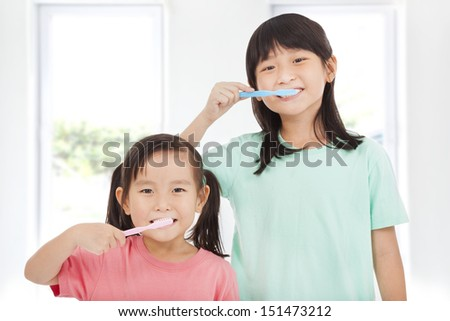 two happy little girls brushing her teeth - stock photo