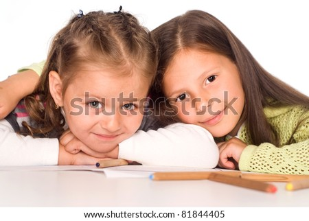 two happy little girls drawing at table - stock photo