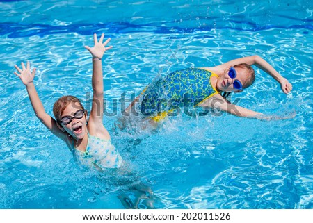 two happy little girls playing  in the swimming pool at the day time - stock photo