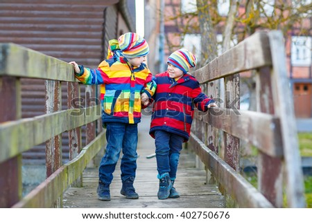 Two happy little kid sibling boys and friends in colorful clothes standing on bridge on spring day. Children having fun together, autumn or spring. Happy, joyful family - stock photo