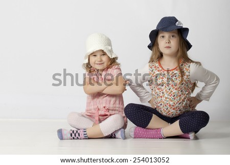 Two happy little sisters isolated on white - stock photo