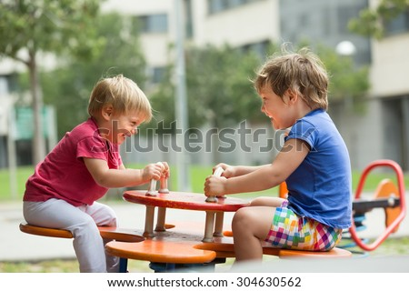 Two happy little sisters playing on teetering board