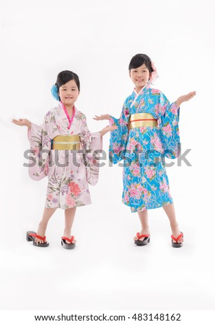 Two happy little sisters wearing a kimono  with hands gesture standing isolated on white