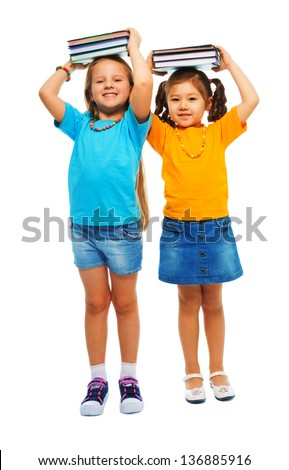 Two happy little 6-7 years old girls holding stack books on their hand and smiling standing isolated on white, full height portrait - stock photo