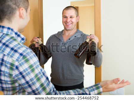 Two happy male friends gathering to drink beer at home  - stock photo