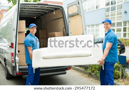 Two Happy Male Workers Putting Furniture And Boxes In Truck - stock photo