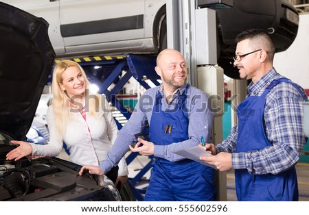 Two happy mechanics and a female driver examine a car at a repair shop