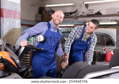 Two happy mechanics checking motorcycles and scooters at a workshop indoors - stock photo