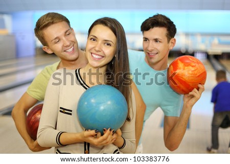 Two happy men and girl hold balls in bowling club; focus on woman; men look at woman; back of boy throwing ball; shallow depth of field - stock photo