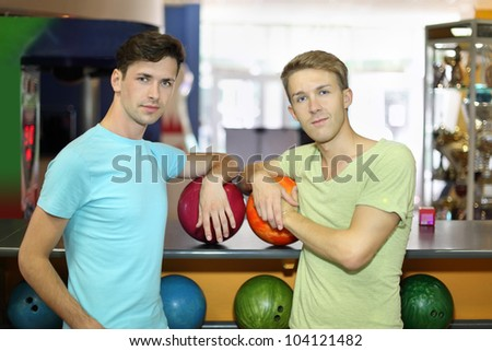Two happy men with balls stand near counter and look at camera in bowling club; shallow depth of field - stock photo