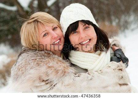 Two happy middle-aged women in winter nature - stock photo