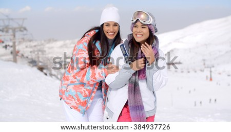 Two happy playful young ladies at a ski resort - stock photo