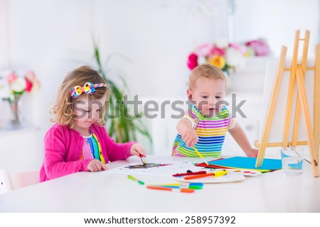 Two happy preschool children, cute little girl and funny toddler boy, painting and drawing together with water color on canvas in a sunny class room with wooden easel, creative young artists at work - stock photo