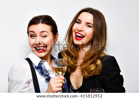 Two  happy pretty gils having fun at party celebrating, showing tongue and smiling, drinking champagne , elegant clothes and hairstyle, flash, white wall. - stock photo