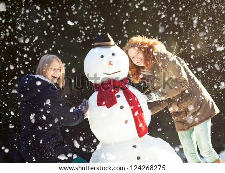 Two happy pretty girls enjoying building a snowman on a snowy winter day