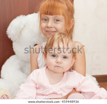Two happy red-haired girl on the big toy bear. The focus in the front baby - stock photo