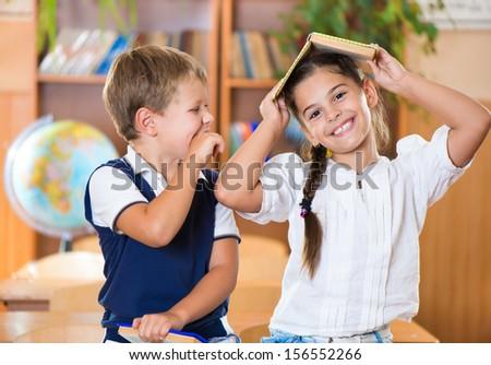 Two happy schoolchildren have fun in classroom at school  - stock photo