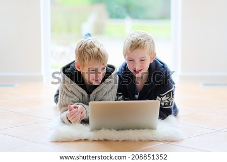 Two happy secondary school boys, twin teenage brothers, studying together doing their homework with notebook laying indoor on the tiles floor - stock photo
