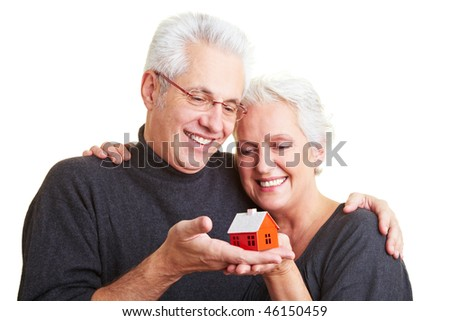 Two happy senior citizens with small red house