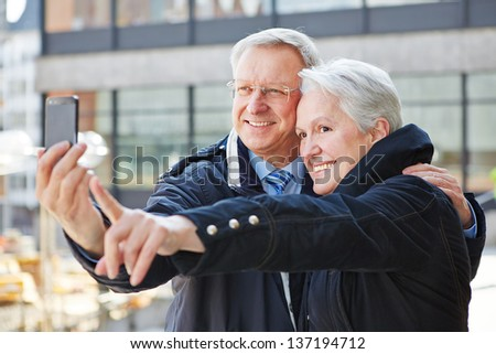 Two happy senior people taking photos with a smartphone - stock photo