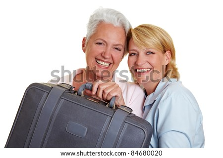 Two happy senior women carrying a grey suitcase - stock photo