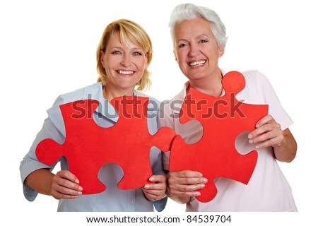 Two happy senior women holding jigsaw puzzle pieces