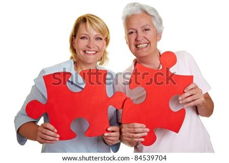 Two happy senior women holding jigsaw puzzle pieces - stock photo