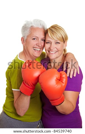 Two happy senior women with red boxing gloves