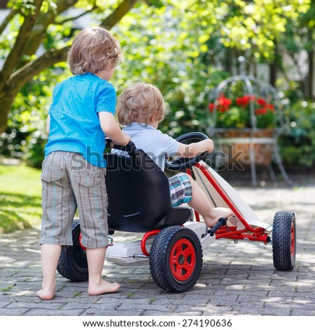 Two happy sibling boys having fun with toy race car in summer garden, outdoors. Adorable brother pushing the car with younger child. From back. Outdoor games for children in summer concept. - stock photo