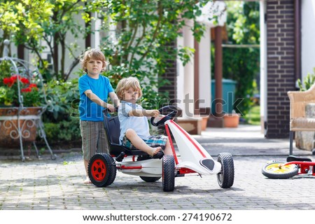 Two happy sibling boys having fun with toy race car in summer garden, outdoors. Adorable brother pushing the car with younger child. Outdoor games for children in summer concept. - stock photo