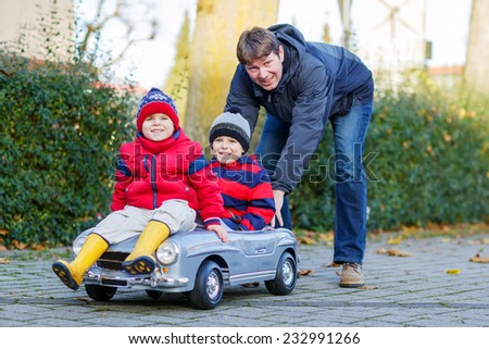 Two happy sibling boys in red jackets and rain boots and their father playing with big old toy car, outdoors. Family and kids leisure on cold day in winter, autumn or spring. - stock photo