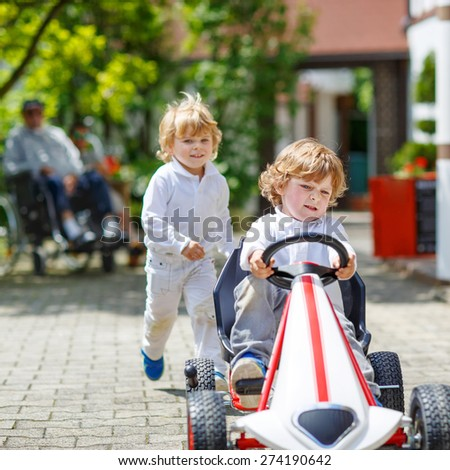 Two happy sibling boys playing with toy car in summer garden, outdoors. Children having fun in domestic garden or nursery on sunny warm day. With grandfather in wheelchair on background - stock photo