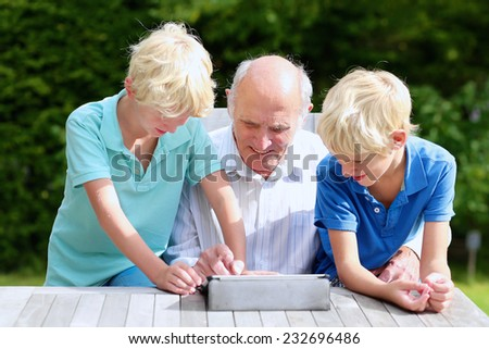 Two happy siblings, twin teenage brothers, spending time together with grandfather, teaching him to use tablet pc, sitting together in the backyard of house on sunny day - stock photo