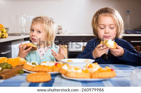 Two happy sisters eating tasty cakes in the kitchen with their mouths full - stock photo