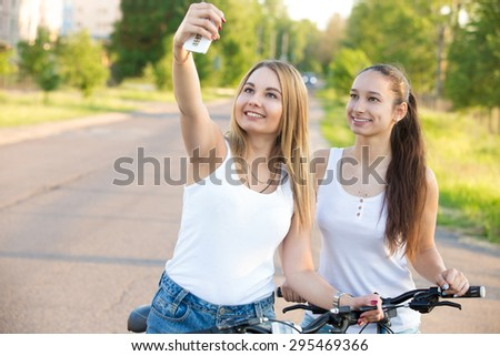 Two happy smiling beautiful young women friends wearing casual clothes standing with bicycles on the road on summer day taking selfie with smartphone, looking at camera, using app device - stock photo