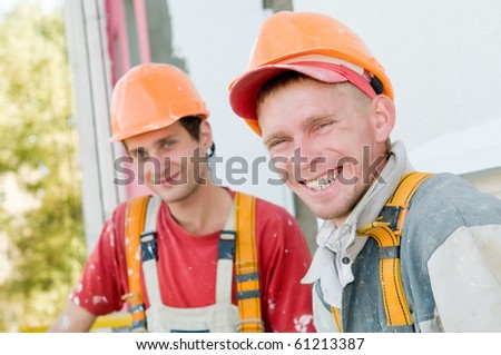 Two happy smiling builder workers facade painters - stock photo