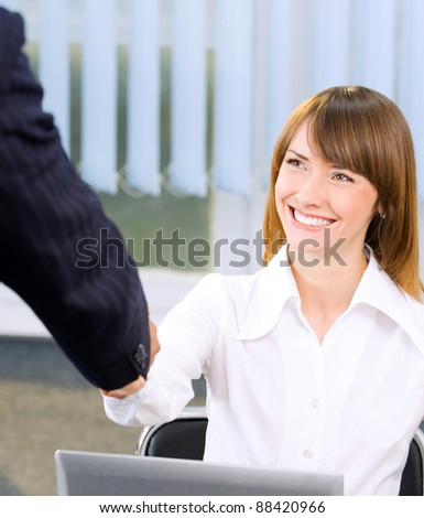 Two happy smiling businesspeople, or business woman and client, handshaking at office - stock photo