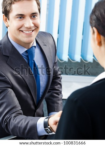 Two happy smiling cheerful businesspeople or business man and client handshaking at office - stock photo
