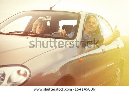 Two happy smiling elderly people in car pointing thumb - stock photo