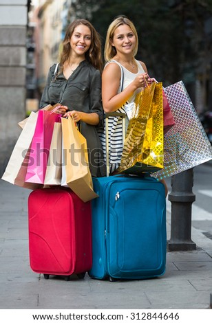 Two happy smiling girls with suitcases and shopping bags standing in the street