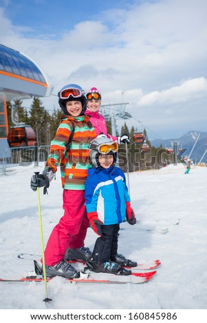 Two happy smiling kids in ski goggles and a helmet with his mother in the mountains - stock photo