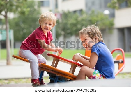 Two happy smiling little sisters on teetering board outdoor