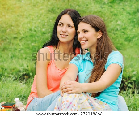 two happy smiling women friends on picnic at the park, lifestyle concept - stock photo