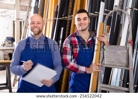 Two happy smiling workmen enjoying of production plan overfulfilment at factory
