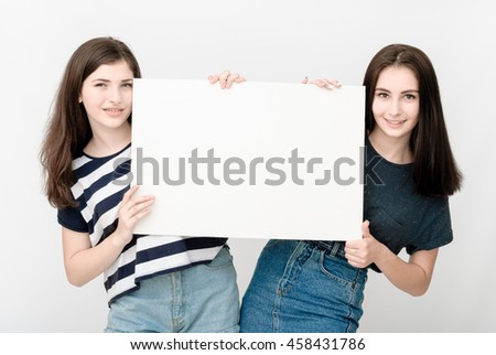 Two happy smiling young business women in casual clothes carrying blank signboard on grey background - stock photo