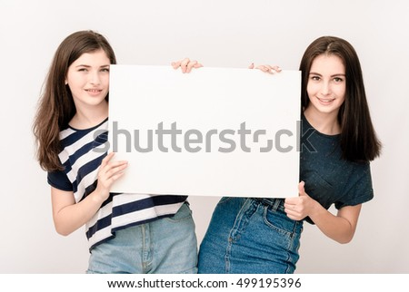 Two happy smiling young business women in casual clothes carrying blank signboard on grey background