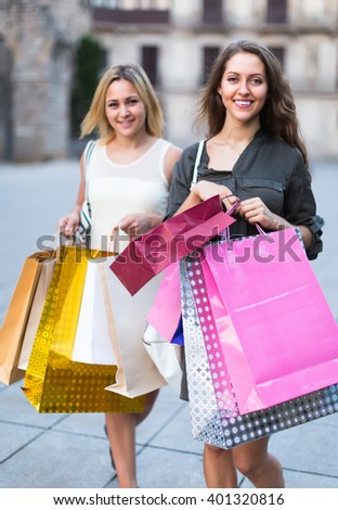 Two happy smiling young women holding many bags after shopping