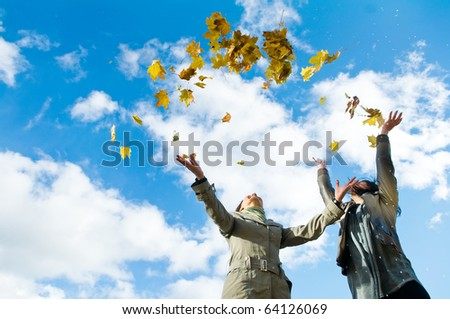 Two happy student girls celebrates autumn by throwing up yellow leafage over blue sky - stock photo