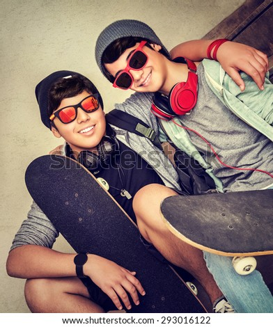 Two happy stylish teen boys sitting on the bench and holding skateboards, cheerful active friends enjoying outdoors sport, fashion teenagers lifestyle - stock photo